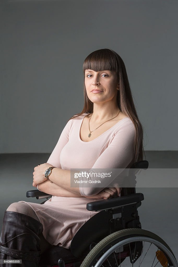 Portrait of confident disabled woman in wheelchair against gray background : Stock Photo