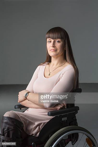 portrait of confident disabled woman in wheelchair against gray background - paraplegic stock photos and pictures