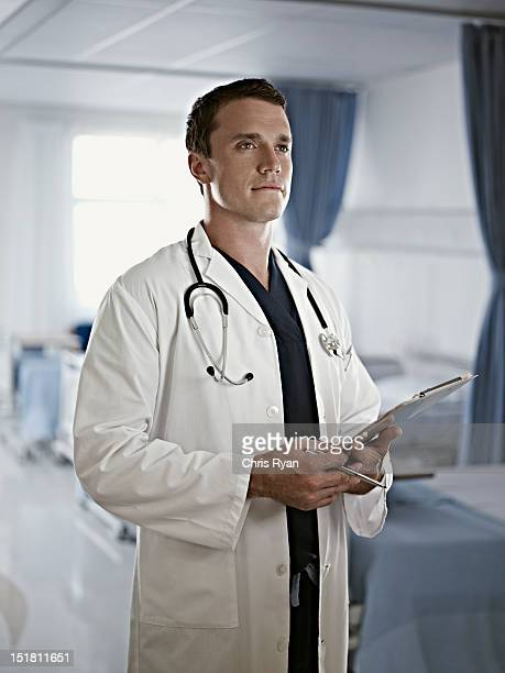 Portrait of confident doctor holding medical record in hospital room
