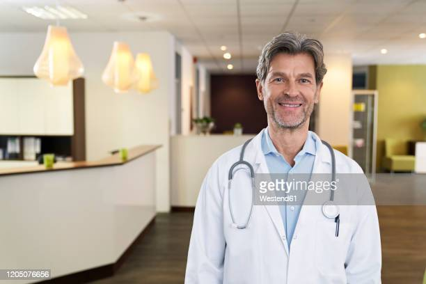 portrait of confident doctor in his medical practice - da cintura para cima imagens e fotografias de stock