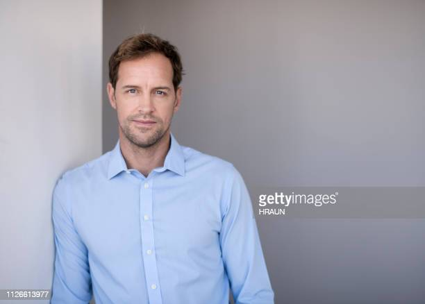 portrait of confident entrepreneur leaning on wall - blue shirt stock pictures, royalty-free photos & images