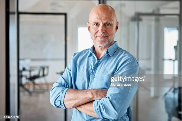 portrait of confident executive with arms crossed - mannen stockfoto's en -beelden