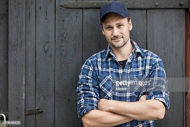 Portrait of confident farmer standing arms crossed against barn door