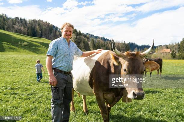 Portrait of confident farmer with cow on pasture