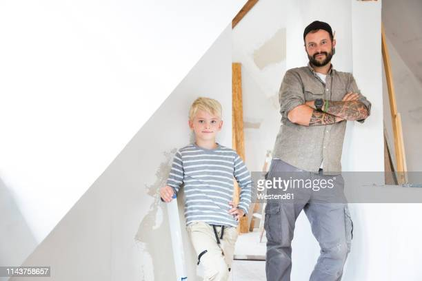 portrait of confident father and son working on loft conversion - lehnend stock-fotos und bilder