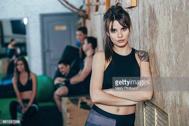 portrait of confident female athlete standing arms crossed with friends in background at health club - arme verschränkt stock-fotos und bilder