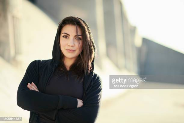 portrait of confident female athlete standing with arms crossed - hooded top stock pictures, royalty-free photos & images