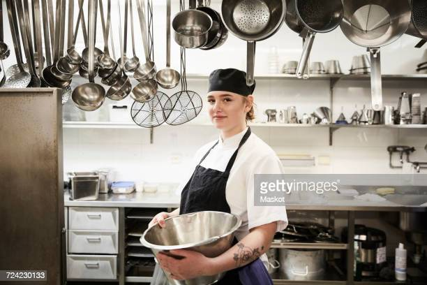 Portrait of confident female chef holding container in commercial kitchen