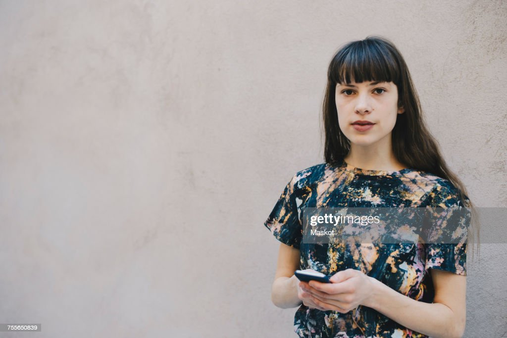 Portrait of confident female computer programmer holding smart phone while standing against beige wall in office : ストックフォト