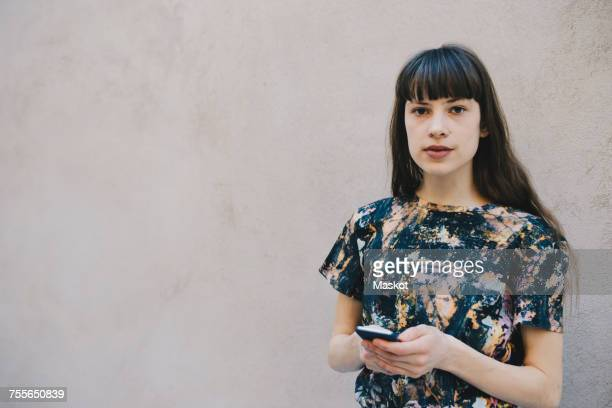 Portrait of confident female computer programmer holding smart phone while standing against beige wall in office