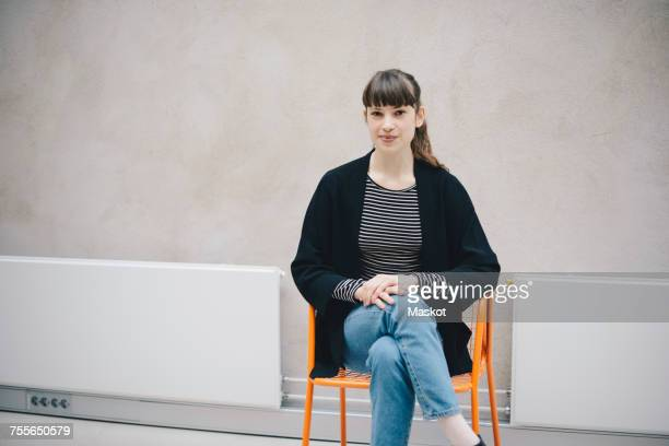 Portrait of confident female computer programmer sitting on chair against beige wall in office
