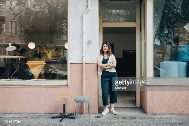 portrait of confident female craftsperson standing at workshop entrance - shop stock-fotos und bilder