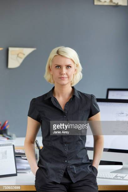 Portrait of confident female designer at office desk