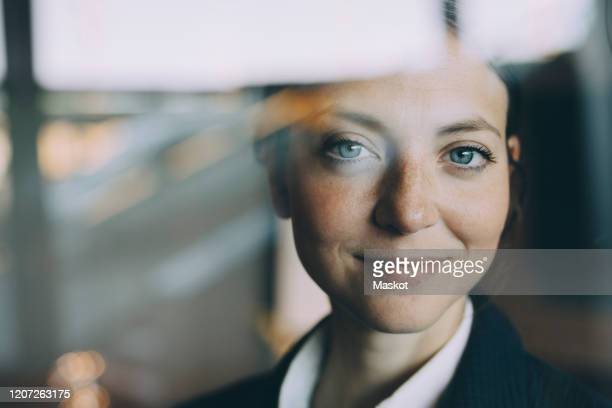 portrait of confident female entrepreneur seen through glass at workplace - photographed through window stock pictures, royalty-free photos & images