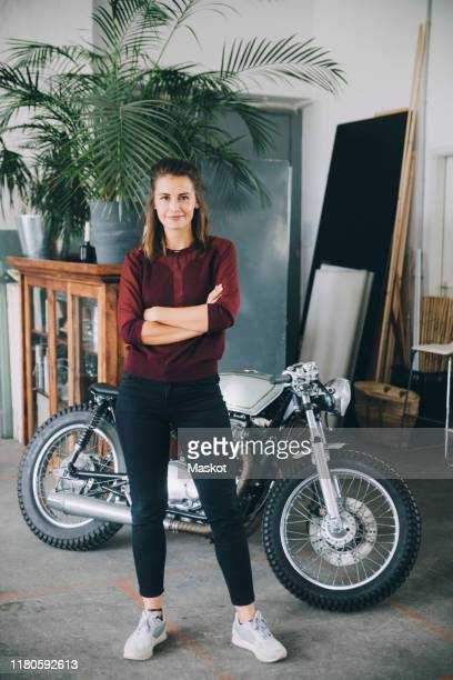 portrait of confident female entrepreneur standing with arms crossed against motorcycle in creative office - standing stock-fotos und bilder