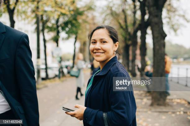 portrait of confident female entrepreneur with phone standing in city - incidental people stock pictures, royalty-free photos & images