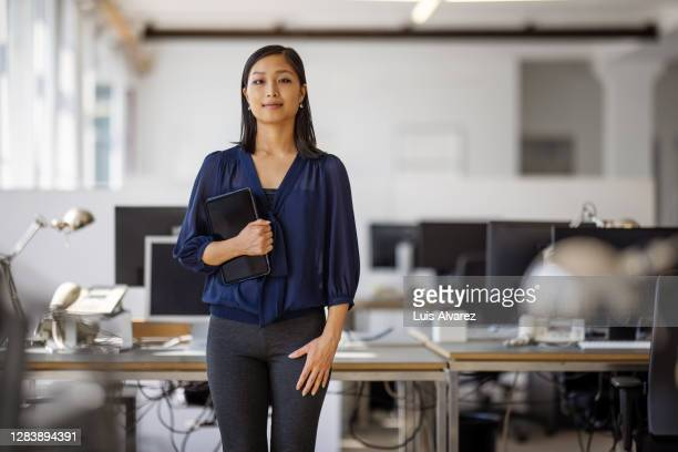 portrait of confident female executive with digital tablet - business stock pictures, royalty-free photos & images