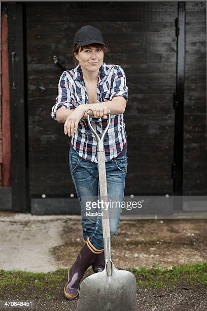 Portrait of confident female farmer with shovel standing against barn