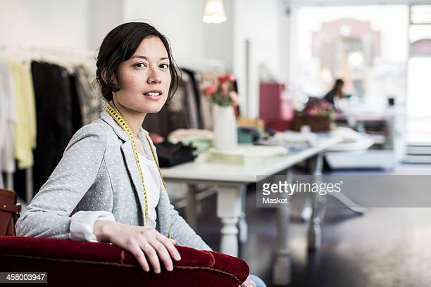 Portrait of confident female fashion designer sitting in studio
