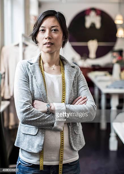 Portrait of confident female fashion designer standing arms crossed in studio