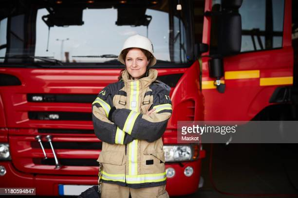 portrait of confident female firefighter standing with arms crossed against fire engine at fire station - rescue worker stock pictures, royalty-free photos & images