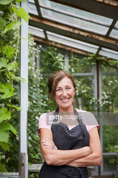 Portrait of confident female gardener standing arms crossed at yard