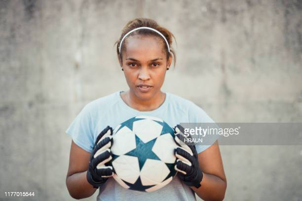 portrait of confident female goalie holding ball - goalie stock pictures, royalty-free photos & images