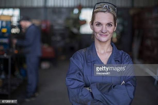 portrait of confident female mechanic in workshop - coveralls stock pictures, royalty-free photos & images