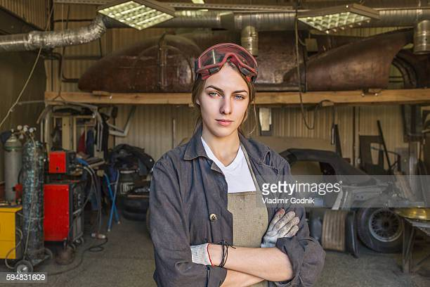 portrait of confident female mechanic with arms crossed at garage - repairman stock pictures, royalty-free photos & images
