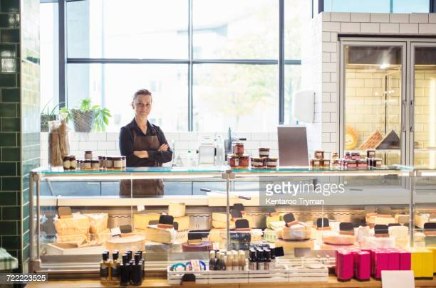 Portrait of confident female owner standing arms crossed at supermarket