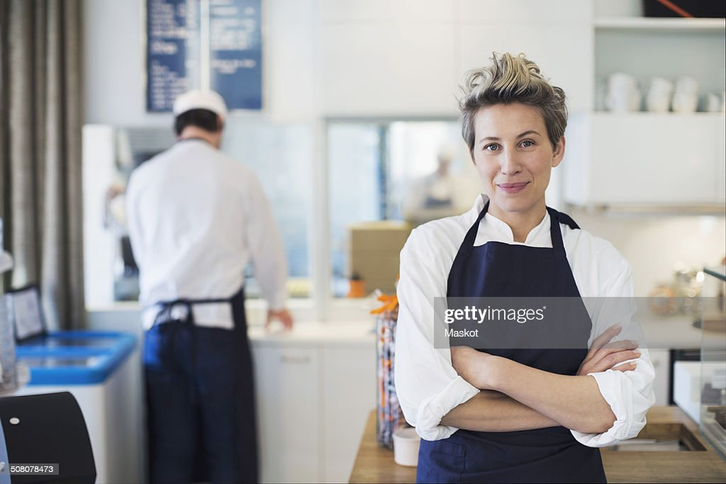 Portrait of confident female owner standing arms crossed in cafe : Stock Photo