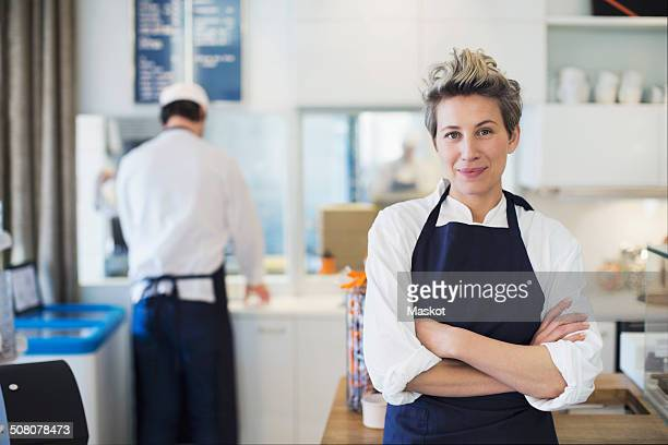 portrait of confident female owner standing arms crossed in cafe - chocolate factory stock photos and pictures