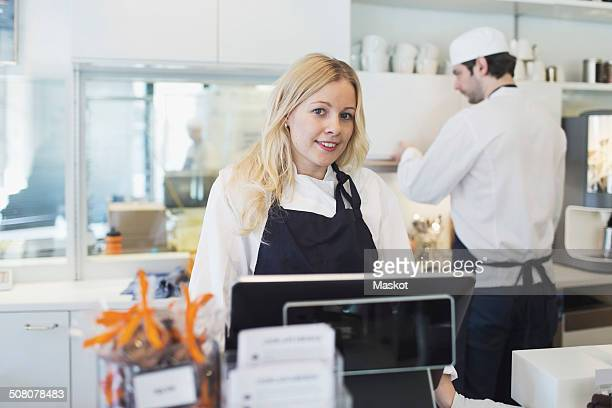 Portrait of confident female owner standing at checkout counter in cafe