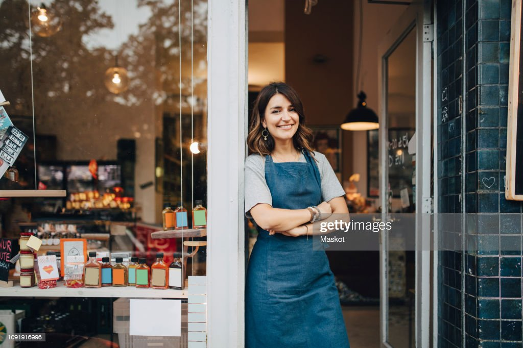 Portrait of confident female owner standing at entrance of deli : Stock-Foto