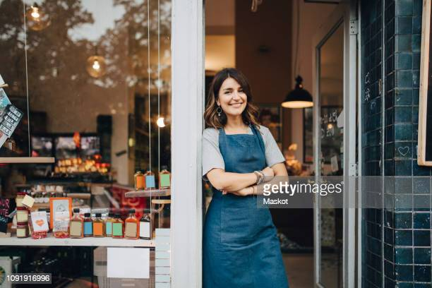 portrait of confident female owner standing at entrance of deli - delicatessen stock pictures, royalty-free photos & images