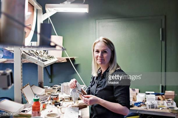Portrait of confident female owner standing at eyeglasses workshop