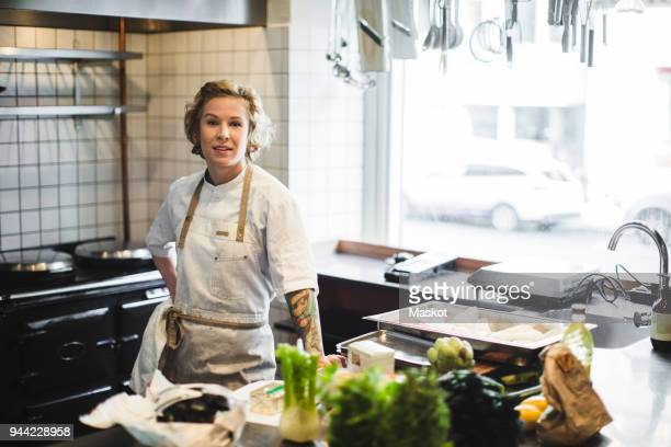 Portrait of confident female owner standing by kitchen counter at restaurant