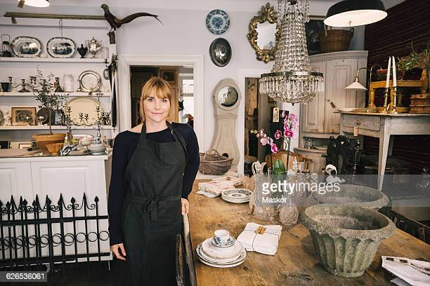 Portrait of confident female owner standing by table in antique store