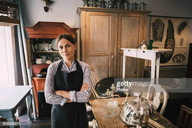 Portrait of confident female owner standing in antique shop