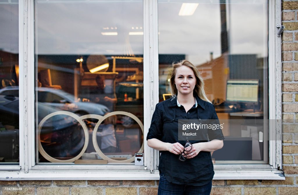 Portrait of confident female owner standing outside eyeglasses workshop : Stock Photo