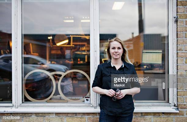 Portrait of confident female owner standing outside eyeglasses workshop
