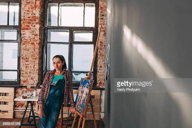 Portrait of confident female painter standing by canvas in studio