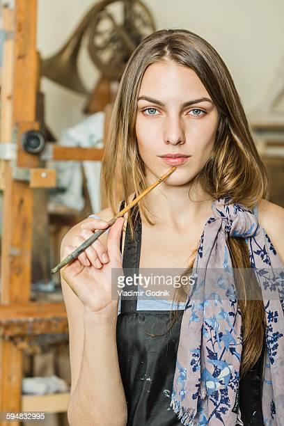 Portrait of confident female painter studio