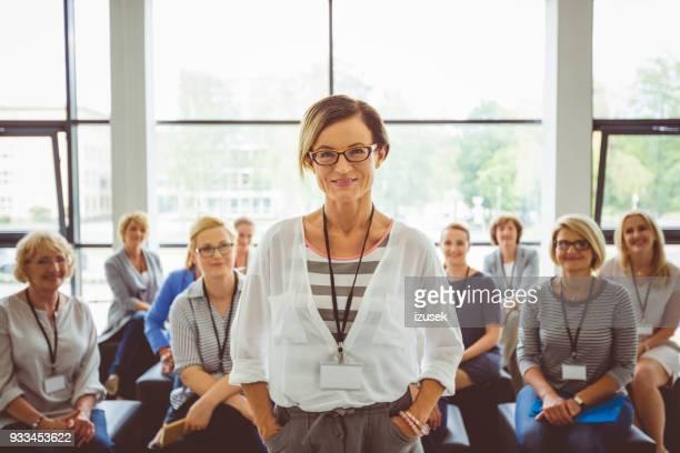 retrato de confianza presentador femenino con público de fondo - igualdad de genero fotografías e imágenes de stock