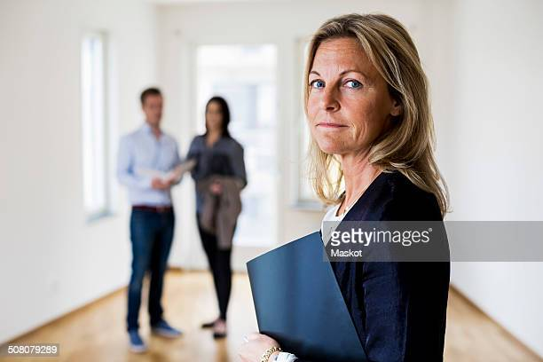 Portrait of confident female real estate agent with couple standing in background at home