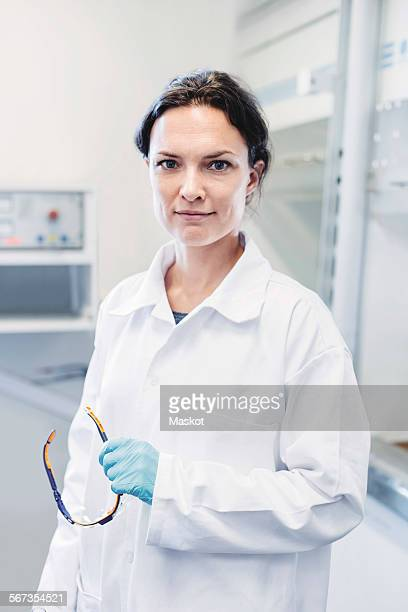 portrait of confident female scientist standing at laboratory - laborkittel stock-fotos und bilder