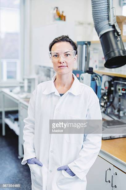Portrait of confident female scientist standing with hands in pockets at laboratory