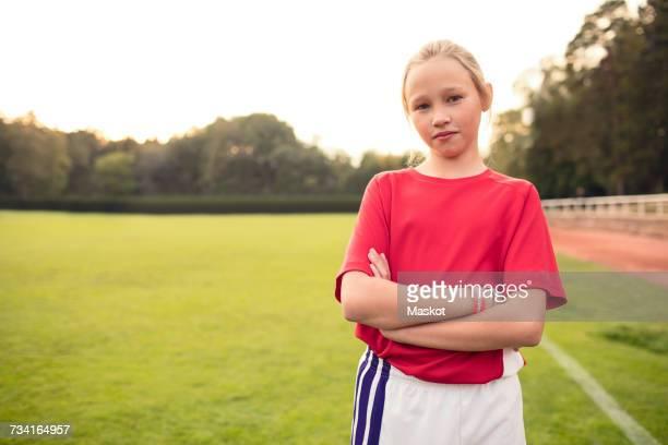 portrait of confident female soccer player standing with arms crossed on field - ein mädchen allein stock-fotos und bilder
