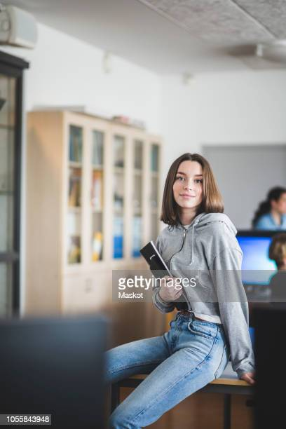 portrait of confident female student sitting with books on desk in classroom at high school - une seule adolescente photos et images de collection