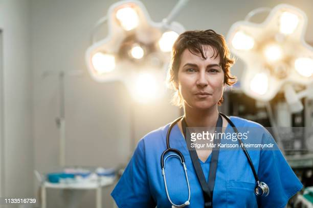 portrait of confident female surgeon in hospital - surgeon stock pictures, royalty-free photos & images